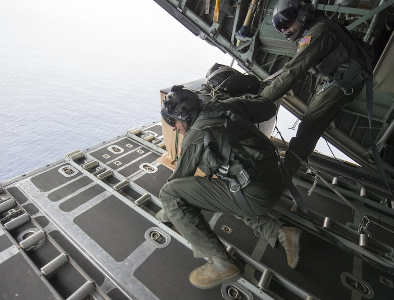 Maj. Bryan Huffman, left, Pacific Air Forces C-130 pilot, checks a drop zone over Ngulu island, Federated States of Micronesia, Dec. 11, 2015, during Operation Christmas Drop. This year marks the 64th year of Operation Christmas Drop and the first time international partners joined in execution through Japan Air Self-Defense Force and Royal Australian Air Force C-130 support. The event provides critical supplies to 56 Micronesian islands impacting about 20,000 people covering 1,000 by 1,800 nautical miles of operation area. (U.S. Air Force photo by Osakabe Yasuo/Released)