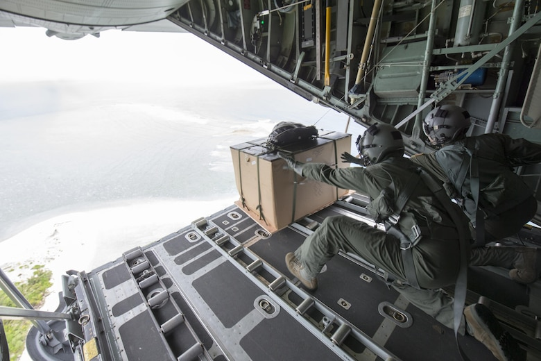 (Left to right) Maj. Bryan Huffman, Pacific Air Forces C-130 pilot, and Staff Sgt. Joel Powell, 36th Airlift Squadron loadmaster, drop a low-cost, low-altitude bundle to Ngulu island, Federated States of Micronesia, Dec. 11, 2015, during Operation Christmas Drop. This is a PACAF event which includes a partnership between the 374th Airlift Wing, Yokota Air Base, Japan; the 36th Wing, Andersen Air Force Base, Guam; the 734th Air Mobility Squadron, Andersen AFB of the 515th Air Mobility Operations Wing, Joint Base Pearl Harbor-Hickam. Hawaii; the University of Guam; and the Operation Christmas Drop private organization. It is the longest-running Department of Defense humanitarian airdrop operation with 2015 being the first trilateral execution with support from Japan Air Self-Defense Force and Royal Australian Air Force. (U.S. Air  Force photo by Osakabe Yasuo/Released)