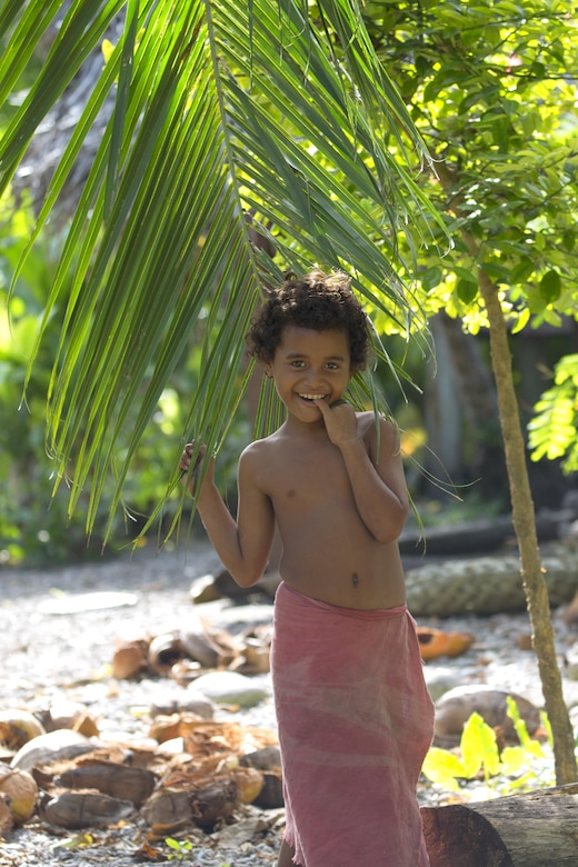 Nigh Hazong, 10, shows his smile under a coconut tree at Fais Island, Federated States of Micronesia, Dec. 8, 2015 during Operation Christmas Drop 2015. Fais Island is a raised coral island in the eastern Caroline Islands in the Pacific Ocean, and forms a legislative district in Yap State in the FSM. Fais Island is located approximately 54 miles east of Ulithi Atoll and 156 miles northeast of Yap. This year marks the first trilateral execution that includes air support from the Japan Air-Self Defense force and the Royal Australian Air Force. (U.S. Air Force photo by Osakabe Yasuo/Released)