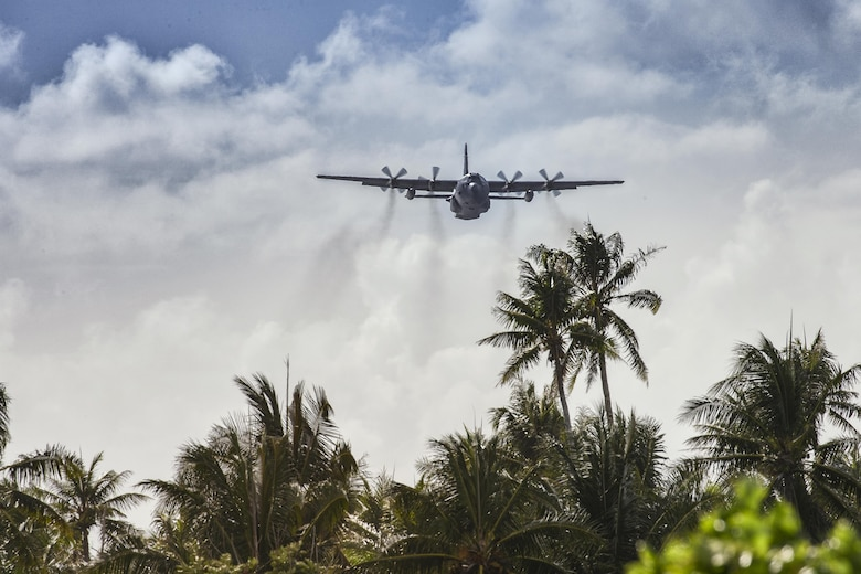 A C-130 Hercules from the 36th Airlift Squadron flies over Fais Island, Dec. 8, 2015, during Operation Christmas Drop 2015. Airmen from the Yokota delivered over 800 pounds of supplies to the island of Fais during Operation Christmas Drop 2015. This year marks the first ever trilateral Operation Christmas Drop where the U.S. Air Force, Japan Air Self-Defense Force and the Royal Australian Air Force work together to provide critical supplies to 56 Micronesian Islands. (U.S. Air Force photo by Osakabe Yasuo/Released)