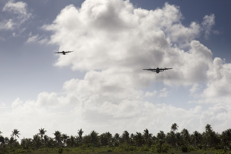 (Left) A Royal Australian Air Force C-130 J Super Hercules and a U.S. Air Force C-130 Hercules from the Yokota Air Base, Japan fly over Fais island, Federated States of Micronesia, Dec. 8, 2015, during Operation Christmas Drop 2015. A  Hercules assigned by the 36th Airlift Squadron delivered over 800 pounds of supplies to Fais Island during Operation Christmas Drop 2015. This year marks the first ever trilateral Operation Christmas Drop where the U.S. Air Force, Japan Air Self-Defense Force and the Royal Australian Air Force work together to provide critical supplies to 56 Micronesian islands.(U.S. Air Force photo by Osakabe Yasuo/Released)
