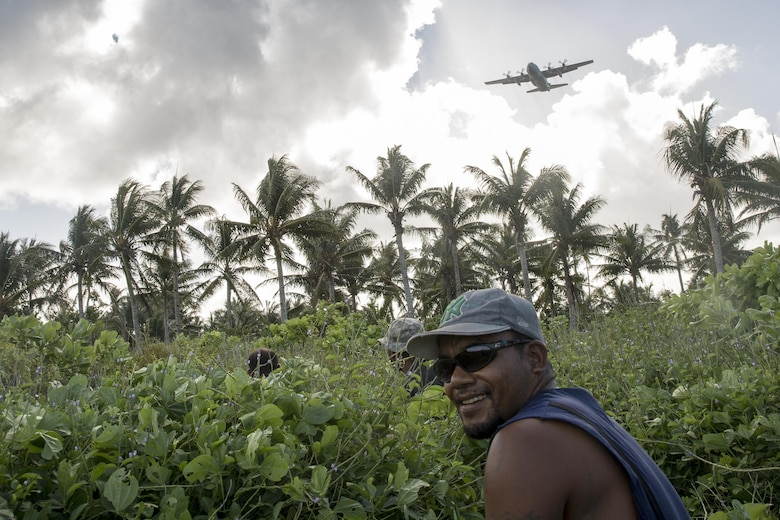 Islanders from Fais sit down to wait for the bundle drop during Operation Christmas Drop 2015, at Fais Island, Federated States of Micronesia, Dec. 8, 2015. A C-130 Hercules assigned to the 36th Airlift Squadron delivered over 800 pounds of supplies to the island of Fais during Operation Christmas Drop 2015. This year marks the first ever trilateral Operation Christmas Drop where the U.S. Air Force, Japan Air Self-Defense Force and the Royal Australian Air Force work together to provide critical supplies to 56 Micronesian islands. (U.S. Air Force photo by Osakabe Yasuo/Released)
