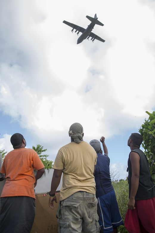 Islanders on Fais island, Federated States of Micronesia, wave to the aircrew of a C-130 Hercules assigned to the 36th Airlift Squadron after dropping a bundle of donated goods and supplies during Operation Christmas Drop 2015, Dec. 8, 2015. Airmen delivered over 800 pounds of supplies to the island of Fais during Operation Christmas Drop 2015. This year marks the first trilateral Operation Christmas Drop where the U.S. Air Force, Japan Air Self-Defense Force and the Royal Australian Air Force work together to provide critical supplies to 56 Micronesian islands impacting 20,000 islanders. (U.S. Air Force photo by Osakabe Yasuo/Released)