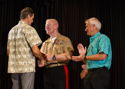 Mark Rigg (left), director, Honolulu Emergency Services Department, receives an award from Lt. Gen. John A. Toolan (middle), commander, U.S. Marine Corps Forces, Pacific, and Mayor Kirk Caldwell (right), City & County of Honolulu, during the First Responder Recognition Ceremony at the Neal S. Blaisdell Center, in Honolulu, Dec. 18, 2015. Various individuals from the Honolulu Emergency Services Department, Honolulu Fire Department, and Honolulu Police Department were recognized for their heroic, selfless actions while responding to a mishap involving an MV-22 tilt-rotor aircraft.