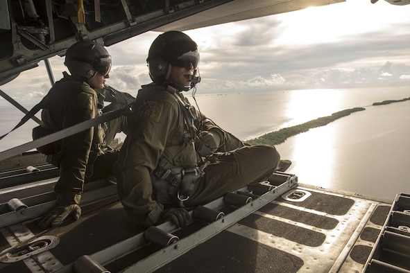 (Right to left) Staff Sgt. Ren Forbes and Airman 1st Class Alexander Lauher, 36th Airlift Squadron loadmasters, watch out the back of a C-130H Hercules after delivering eight bundles to Mortlock Islands, Federated States of Micronesia, Dec. 9, 2015, during Operation Christmas Drop. Every December, C-130H Hercules aircrews from Yokota head to Andersen Air Force Base to execute low-cost, low-altitude humanitarian airdrops to islanders throughout the Commonwealth of the Northern Marianas, Federated States of Micronesia, Republic of Palau. These islands are some of the most remote locations on the globe spanning a distance nearly as broad as the continental U.S. It is the longest-running Department of Defense humanitarian airdrop operation with 2015 being the first trilateral execution with support from Japan Air Self-Defense Force and Royal Australian Air Force. (U.S. Air Force photo by Osakabe Yasuo/Released)