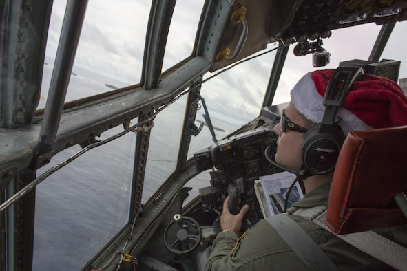 Cant. John Menezes, 36th Airlift Squadron C-130 pilot, looks down his window while flying a C-130 Hercules through islands near Ettal Atoll, Federated Sates of Micronesia, Dec. 9, 2015, during Operation Christmas Drop. This is a humanitarian aid/disaster relief training event where C-130 aircrews perform low-cost low-altitude airdrops on unsurveyed drop zones while providing critical supplies to 56 islands throughout the Commonwealth of the Northern Marianas, Federated States of Micronesia and Republic of Palau. It highlights the U.S. and allied airpower capabilities to orient and respond to activities in peacetime and crisis. In addition to delivering critical supplies to those in need, Operation Christmas Drop provides specific training to U.S. and allied aircrews, enabling theater-wide airpower. (U.S. Air Force photo by Osakabe Yasuo/Released)