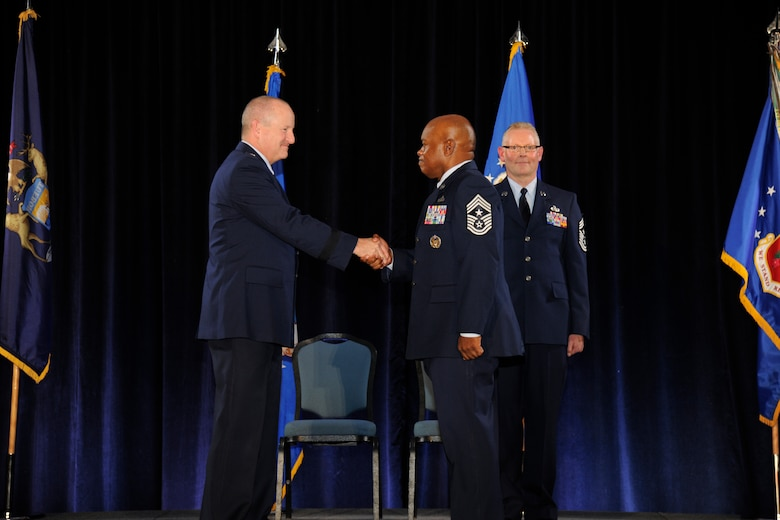 Brig. Gen. John D. Slocum, 127th Wing commander, shakes hands with newly-appointed 127th Wing Command Chief Master Sgt. Tony Whitehead during the 127th Wing Annual Awards Ceremony at Selfridge Air National Guard Base, Mich., Dec. 5, 2015. Behind Slocum and Whitehead is Chief Master Sgt. Robert Dobson, who completed his service as the Wing's command chief during the ceremony. (U.S. Air National Guard photo by Senior Airman Ryan Zeski)