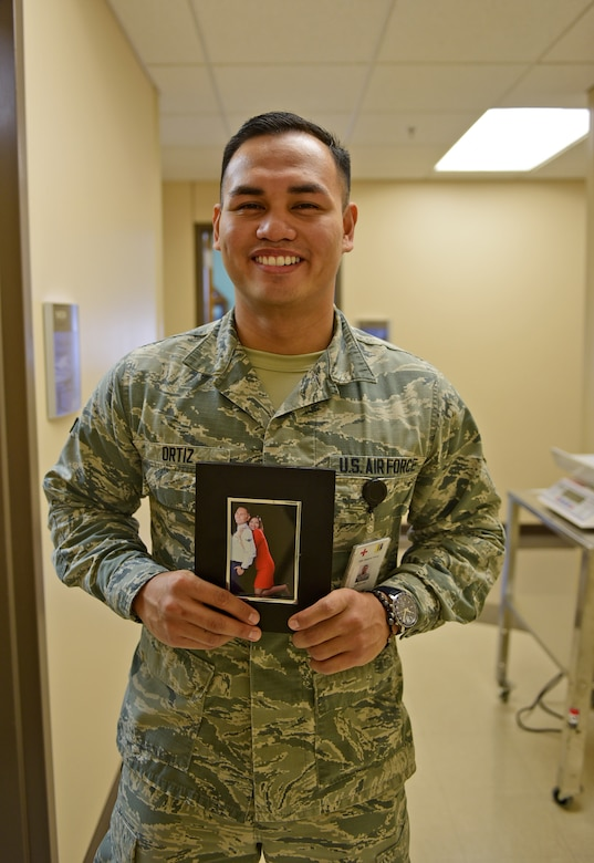 Airman 1st Class Emilcarlo Ortiz, 28th Medical Operations Squadron aerospace medical technician, stands with a photo of him and his fiancé Weynmhe at Ellsworth Air Force Base, S.D., Nov. 20, 2015. His family currently resides in the Philippines, however, Ortiz uses the photo as a daily reminder of what he is thankful for. (U.S. Air Force photo by Airman 1st Class James L. Miller/Released)