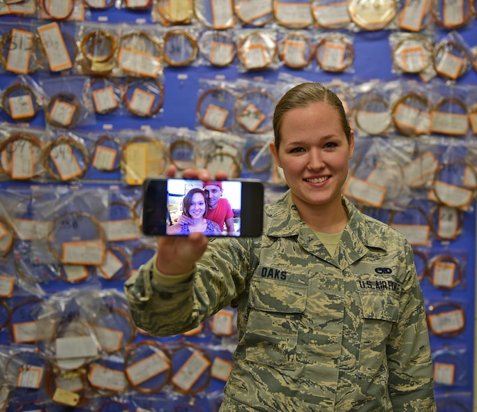 Airman 1st Class Stacy Oaks, 28th Maintenance Squadron electrical and environmental systems apprentice, stands with a photo of her and her husband, Josh, at Ellsworth Air Force Base, S.D., Nov. 20, 2015. Even though she will not be able to go home this holiday season, Oaks is thankful she can still spend time with her husband. (U.S. Air Force illustration by Airman 1st Class James L. Miller/Released)