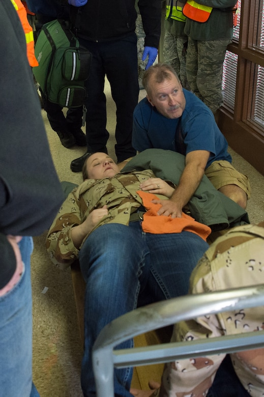 U.S. Air Force Master Sgt. Tim Merritt, 153rd Logistics Readiness Squadron tends to Senior Airman Karen Klein's simulated wounds, Dec. 18, 2015 at Cheyenne Air National Guard base in Cheyenne, Wyoming. Merritt performed self-aid and buddy care on Klein and other simulated victims during an active shooter exercise. The scenario was in support of memorandum sent by Secretary of the Air Force Deborah James to test lockdown and active shooter procedures in response to shootings in Chattanooga, Tenn. (U.S. Air National Guard photo by Master Sgt. Charles Delano)