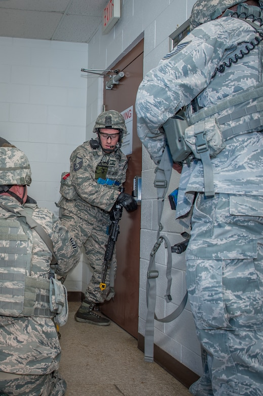 U.S. Air Force Master Sgt. Gregory Wardle, 153rd Security Forces Squadron, communicates with Airmen on the other side of a locked door, Dec. 18, 2015 at Cheyenne Air National Guard base in Cheyenne, Wyoming. Wardle and several security forces Airmen clear buildings and check for wounded after eliminating a gunman during an active shooter exercise. The scenario was in support of memorandum sent by Secretary of the Air Force Deborah James to test lockdown and active shooter procedures in response to shootings in Chattanooga, Tenn. (U.S. Air National Guard photo by Master Sgt. Charles Delano)