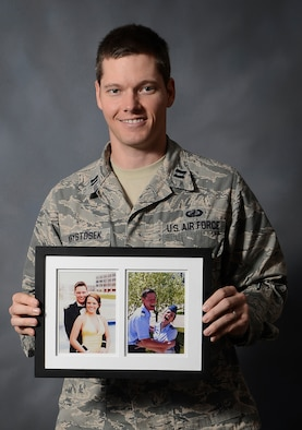 Capt. Timothy Krystosek, a budget analyst assigned to the U.S. Central Command, holds a picture frame with photos of him and his wife, 1st Lt. Lauren Krystosek, Dec. 9, 2015, at MacDill Air Force Base, Fla. Every other weekend, Timothy makes a seven-hour trip north to Eglin Air Force Base, Fla., where Lauren is stationed. (U.S. Air Force photo by Airman 1st Class Mariette M. Adams)