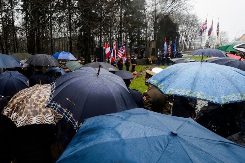 More than 50 spectators hold up umbrellas during a Battle of the Bulge anniversary ceremony at the National Liberation Memorial in Schumanns Eck, Luxembourg, Dec. 16, 2015. The community erected the memorial in 1994 to commemorate the 50th anniversary of the Battle of the Bulge. (U.S. Air Force photo by Staff Sgt. Christopher Ruano/Released)