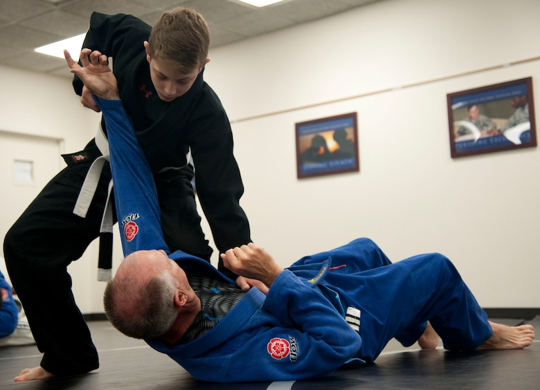 Justus Walker, 12, works on knee-on-belly drills with retired Army Col. Paul Bischoff during Jiu Jitsu practice at the Community Chapel Activity Center at Vance Air Force Base, Oklahoma Nov. 19. Jiu Jitsu, a form of martial arts, is offered twice a week through chapel. (U.S. Air Force photo / Staff Sgt. Nancy Falcon)