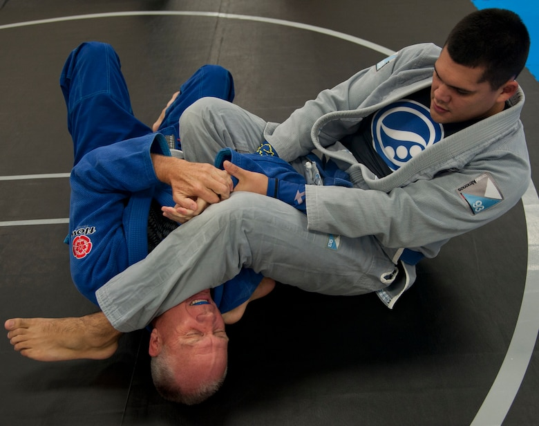 Senior Airman Oscar Felix, an air traffic controller with the 71st Operations Support Squadron, grapples with retired Army Col. Paul Bischoff Nov. 19 at the Community Chapel Activity Center at Vance Air Force Base, Oklahoma. Jiu Jitsu, a form of martial arts, was bought to Vance nearly two years ago by Tech. Sgt. Tony Eclavea, a chaplain assistant with the 71st Flying Training Wing. (U.S. Air Force photo / Staff Sgt. Nancy Falcon)