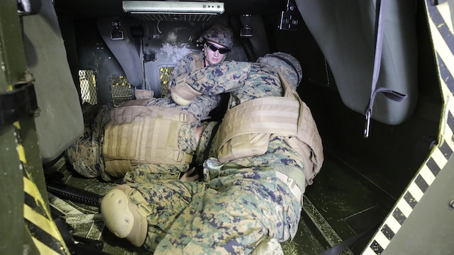 Marines with 2nd Supply Battalion, 2nd Marine Logistics Group rehearses life-saving techniques on a fellow Marine during a Humvee Egress Assistance Trainer class at Marine Corps Base Camp Lejeune, N.C., Dec. 17, 2015.  The HEAT class is designed to show Marines what to do if a vehicle rolls over during low visibility, no visibility, or experiences sideways or 180-degree rollovers.