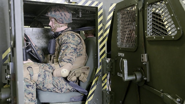 A Marine with 2nd Supply Battalion, 2nd Marine Logistics Group sits in the driver seat of a simulator during a Humvee Egress Assistance Trainer class at Marine Corps Base Camp Lejeune, N.C., Dec. 17, 2015.  The HEAT class is designed to show Marines what to do if a vehicle rolls over during low visibility, no visibility, or experiences sideways or 180-degree rollovers.