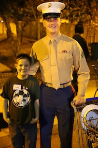 "Kaden Jeide (left) and Cpl. Matthew Franzoni, pose for a picture after spending the night shopping for Christmas presents as part of a ""holiday with Heroes"" event held in Poway, California, December 10. During the city-funded event, children purchased presents for their families and friends, took holiday photos with Santa, built arts and crafts, and participated in other events throughout the Night. (USMC photo by Cpl. Jonathan Boynes)"