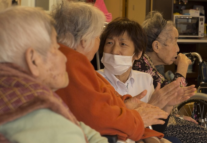 Residents of the Vita Nursing Home in Iwakuni, Japan, give applause toward the station volunteers from Marine Corps Air Station Iwakuni Dec. 16, 2015. The chapel coordinated this community even as an opportunity to experience Japanese culture, give back to the local community and strengthen the bond between the U.S. and Japan. Volunteers sang Christmas carols, provided baked goods and gifts and provided residents with a sense of holiday spirit.