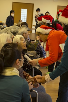 Volunteers from Marine Corps Air Station Iwakuni, Japan, wish residents at the Vita Nursing Home in Iwakuni, a merry Christmas after caroling on Dec. 16, 2015. The chapel coordinated this community even as an opportunity to experience Japanese culture, give back to the local community and strengthen the bond between the U.S. and Japan. Nursing home residents expressed happiness, appreciation and shed tears of joy toward the residents.