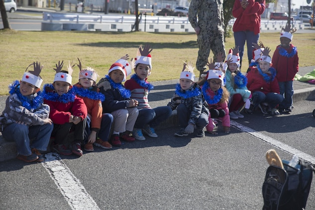 Students of Matthew C. Perry Elementary School at Marine Corps Air Station Iwakuni, Japan, display their hand-made holiday arts and crafts during the Jingle Bell Jog at the IronWorks Gym Dec. 18, 2015. The Jingle Bell Jog is an event for service members and their families to show off their holiday spirit as they run through the station. Events like this help raise spirits and build camaraderie during the holiday season while most service members are away from their families.