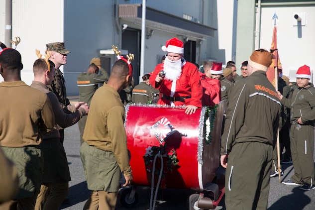 Marines with Combat Logistics Company 36 inspect Santa's sleigh before kicking off the annual 1.5k Jingle Bell Jog at the IronWorks Gym, Marine Corps Air Station Iwakuni, Japan, Dec. 18, 2015. The Jingle Bell Jog is an event for service members and their families to show off their holiday spirit as they run through the station. Events like this help raise spirits and build camaraderie during the holiday season while most service members are away from their families.