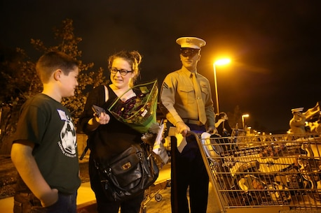 "Kaden Jeide (left), Spencer Jeide (center), and Cpl. Matthew Franzoni, stand outside of a shopping center during a ""holiday with Heroes"" event held in Poway, California, December 10. During the city-funded event, children purchased presents for their families and friends, took holiday photos with Santa, built arts and crafts, and participated in other events throughout the night. Franzoni is a gunner with 1st LAR. (USMC photo by Cpl. Jonathan Boynes)"