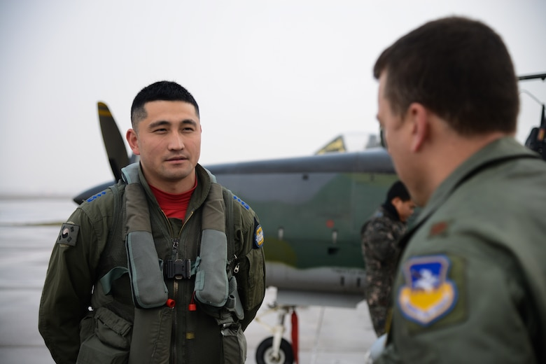 Republic of Korea air force Capt. Park Jung Hun, 237th Fighter Squadron, Wonju Air Base, KA-1 Woongbi pilot speaks with Maj. Craig Morash, 25th Fighter Squadron pilot and director of operations, after arriving for Buddy Wing 15-8 at Osan AB, ROK, Dec. 15, 2015. Buddy Wing ensures combat readiness and training for combined operations between the U.S. Air Force and ROKAF. (U.S. Air Force photo/Airman 1st Class Dillian Bamman)
