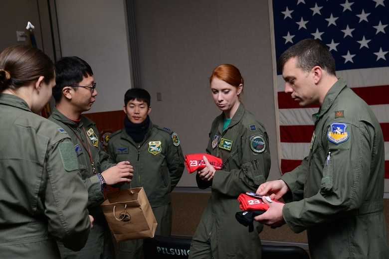 U.S. Air Force and Republic of Korea air force pilots exchange squadron gifts during Buddy Wing 15-8 at Osan Air Base, ROK, Dec. 18, 2015. The pilots exchanged their squadron's patches and t-shirts before the ROKAF pilots depart Osan. (U.S. Air Force photo/Airman 1st Class Dillian Bamman)
