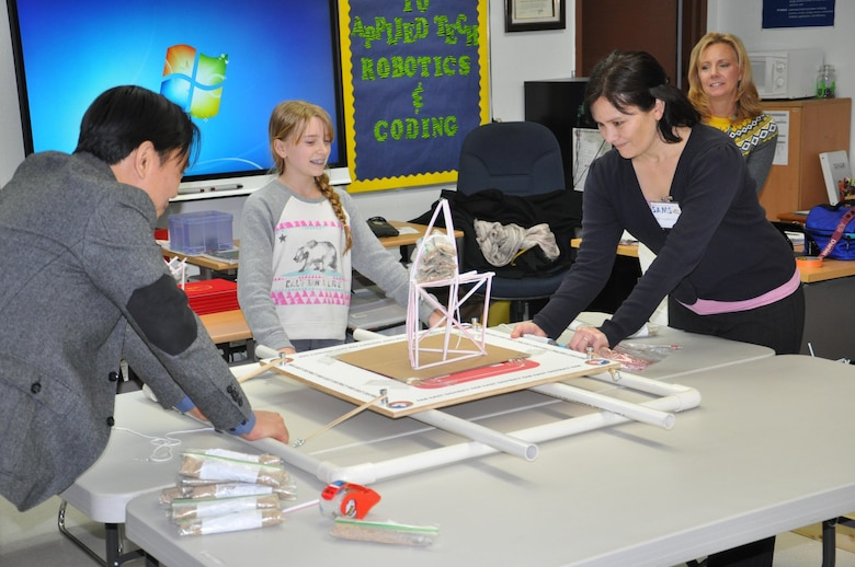 Seoul American Middle School student Hannah Sullivan prepares to see if her tower can withstand the force of an earthquake as Far East District science, technology, engineering and math coordinator Pam Lovasz (right), Seoul American Middle School applied technology teacher Kelly Brock (far right) and district engineering division design branch chief Son Ha (left) look on.