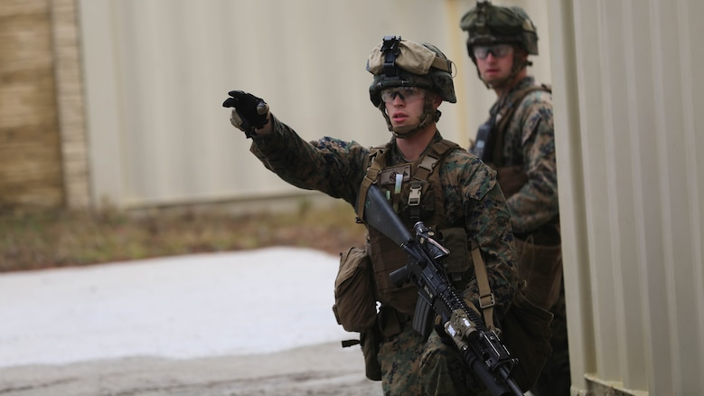 Lance Cpl. Trevor Lancaster, a rifleman with 3rd Battalion, 6th Marine Regiment, gives direction during a limited objective experiment at Marine Corps Base Camp Lejeune, N.C., Dec. 8, 2015. The Marine Corps Warfighting Laboratory worked with 3rd Bn., 6th Marines, and 1st Battalion, 10th Marine Regiment, to test artillery and infantry integration tactics. During the experiment, the company landing team attacked from near the Onslow Beach landing site towards the objective of the Military Operation in Urban Terrain training center. (U.S. Marine Corps photo by Cpl. Michael Dye/Released)