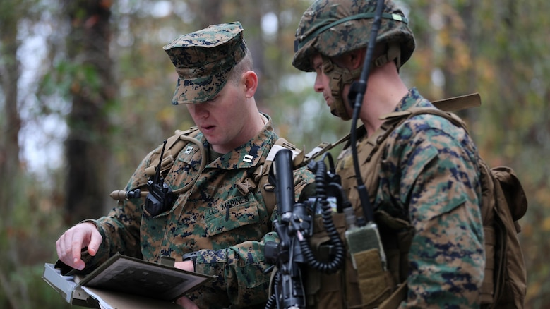 (Left) Captain Jerald Feehery, a project officer for Marine Corps Warfighting Laboratory, discusses tactics with Capt. Patrick Parks, the Lima Company commander with 3rd Battalion, 6th Marine Regiment, prior to entering the Military Operation in Urban Terrain during a limited objective experiment at Marine Corps Base Lejeune, N.C., Dec. 8, 2015. The Marine Corps Warfighting Laboratory worked with 3rd Bn., 6th Marines, and 1st Battalion, 10th Marine Regiment, to test artillery and infantry integration tactics. During the experiment, the company landing team attacked from near the Onslow Beach landing site towards the objective of the Military Operation in Urban Terrain training center.