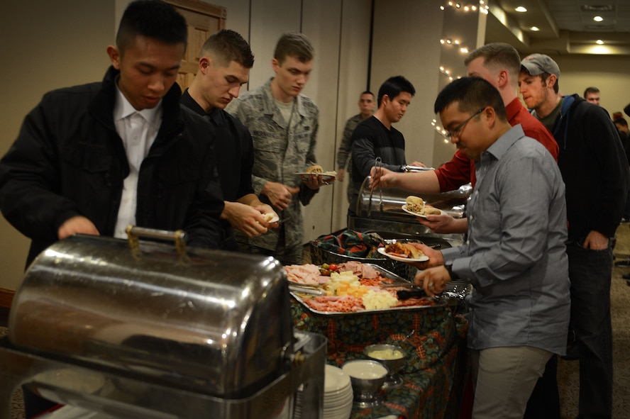 Cannon Airmen load their plates with food during the Single Airmen Christmas party Dec. 16, 2015, at Cannon Air Force Base, N.M. The annual event is sponsored courtesy of nearby Clovis and the Committee of Fifty, a local organization that supports Cannon and its Air Commandos. (U.S. Air Force photo/Staff Sgt. Matthew Plew)