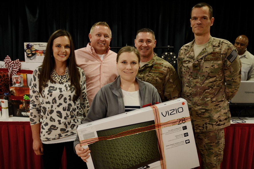 """U.S. Air Force Senior Airman Sarah Filbin, 27th Special Operations Aerospace Medicine Squadron, wins a 28"""" television set during the Single Airmen Christmas party Dec. 16, 2015, at Cannon Air Force Base, N.M. Filbin posed for a photo with Clovis Committee of Fifty members Sarah and Justin Stagner, Chief Master Sgt. Randy Scanlan, 27th Special Operations Wing command chief, and Col. Ben Maitre, 27th SOW commander, after her winning ticket was drawn. (U.S. Air Force photo/Staff Sgt. Matthew Plew)"""