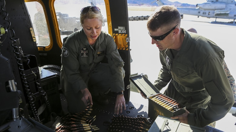 Sgt. Elizabeth M. Azcuenaga explains to 1st. Lt. James E. Shelton how to properly feed GAU-21/A .50 Caliber Machine Gun ammunition in order to reduce double feeds and jams in preparation for a Joint Terminal Attack Control training scenario Dec. 15, at Marine Corps Base Camp Pendleton, California. Azcuenaga, a Donnelly, Idaho, native, is a weapons and tactics instructor with Marine Light Attack Helicopter Squadron 169, Marine Aircraft Group 39, 3rd Marine Aircraft Wing. Shelton, a San Luis Obispo, California, native, is an aerial observer with HMLA-169, MAG 39, 3rd MAW.
