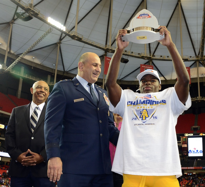 Maj Gen Richard S. Haddad hands out the offensive MVP award to North Carolina A&T's Tarik Cohen  who rushed for 295 touchdowns and three touchdowns of 73 or more yards Saturday. North Carolina A&T won the thriller 41-34 over Alcorn State in the Air Force Reserve Celebration Bowl at the Georgia Dome. (Air Force photo/Master Sgt. Chance Babin)
