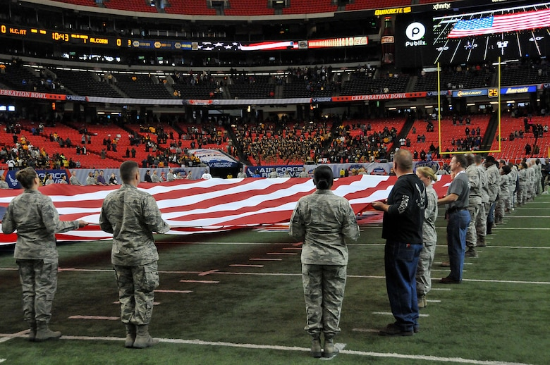 Airmen and a few family members unfurl the flag at the inaugural Air Force Reserve Celebration Bowl Dec. 19 at the Georgia Dome in Atlanta. It took nearly 60 people to unfurl the massive flag. (U.S. Air Force photo/Senior Airman Andrew Park)
