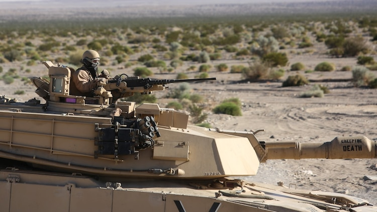A Marine mans the turret of an M1A1 Abrams tank during the mechanized assault portion of a Marine Corps Combat Readiness Evaluation at Marine Corps Air Ground Combat Center Twentynine Palms, Calif., Dec. 8, 2015. The purpose of a MCCRE is to evaluate Marines' collective performance in specific mission requirements  that will prepare them for their upcoming deployment rotation. The Marine is with 1st Tank Battalion, 1st Marine Division. (U.S. Marine Corps photo by Lance Cpl. Devan K. Gowans)