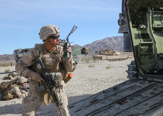 Cpl. Dustin Deloris relays orders over the radio during the mechanized assault portion of the Marine Corps Combat Readiness Evaluation at Marine Corps Air Ground Combat Center Twentynine Palms, Calif., Dec. 8, 2015. The purpose of a MCCRE is to evaluate Marines' collective performance in specific mission requirements that will prepare them for their upcoming deployment rotation. Deloris is a team leader with Company E, 2nd Battalion, 7th Marine Regiment, 1st Marine Division. (U.S. Marine Corps photo by Lance Cpl. Devan K. Gowans)