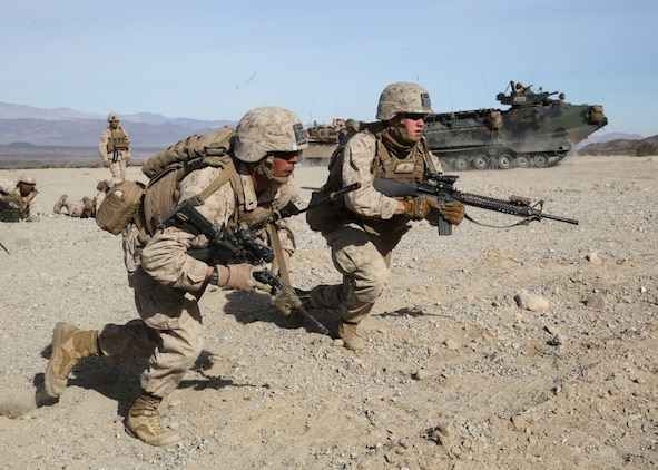 Marines rush a simulated combat town during the mechanized assault portion of a Marine Corps Combat Readiness Exercise at Marine Corps Air Ground Combat Center Twentynine Palms, Calif., Dec. 9, 2015. The purpose of a MCCRE is to evaluate Marines' collective performance in specific mission requirements  that will prepare them for their upcoming deployment rotation. The Marines are with 2nd Battalion, 7th Marine Regiment, 1st Marine Division. (U.S. Marine Corps photo by Lance Cpl. Devan K. Gowans)