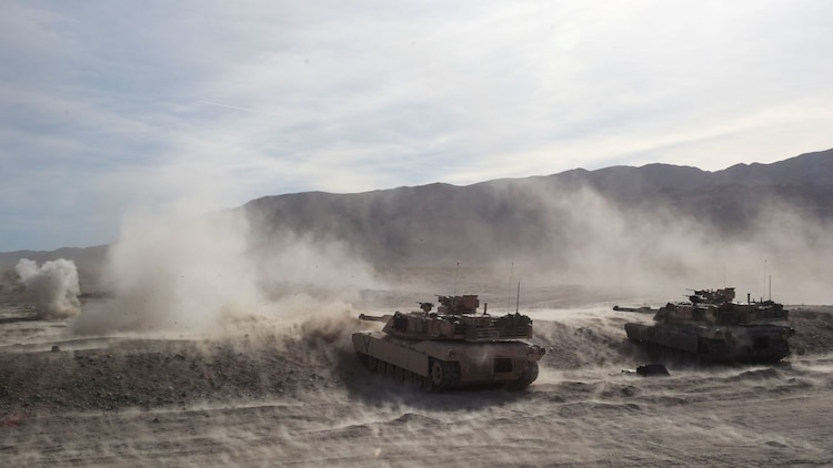 M1A1 Abrams tanks fire on targets during the mechanized assault portion of a Marine Corps Combat Readiness Evaluation at Marine Corps Air Ground Combat Center Twentynine Palms, Calif., Dec. 8, 2015. The purpose of a MCCRE is to evaluate Marines' collective performance in specific mission requirements that will prepare them for their upcoming deployment rotation. The tanks are supporting 2nd Battalion, 7th Marine Regiment, 1st Marine Division. (U.S. Marine Corps photo by Lance Cpl. Devan K. Gowans)