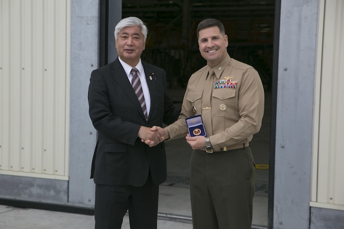 Gen Nakatani, Japanese Defense Minister, presents Col. Robert V. Boucher, commanding officer of Marine Corps Air Station Iwakuni, Japan, with a gift after Nakatani's tour of Marine Aerial Refueler Transport Squadron (VMGR) 152 facilities during his visit to the air station, Dec. 2, 2015. As part of the growing U.S. – Japan relationship, this visit provided Nakatani an opportunity to connect with station officials and view pertinent installation facilities that aid in the Marine Corps' mission success.