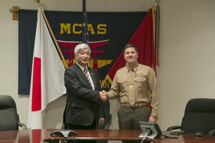 Colonel Robert V. Boucher, commanding officer of Marine Corps Air Station Iwakuni, Japan, greets Gen Nakatani, Japanese Defense Minister, during Nakatani's visit to the air station, Dec. 2, 2015. As part of the growing U.S. – Japan relationship, this visit provided Nakatani an opportunity to connect with station officials and view pertinent installation facilities that aid in the Marine Corps' mission success.