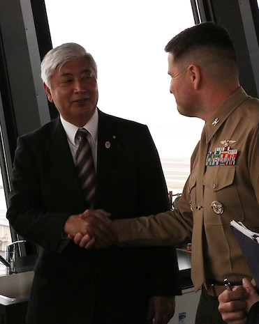 Gen Nakatani, Japanese Defense Minister, thanks Col. Robert V. Boucher, commanding officer of Marine Corps Air Station Iwakuni, Japan, during a station visit to the air traffic control tower, Dec. 2, 2015. As part of the growing U.S. – Japan relationship, this visit provided Nakatani an opportunity to connect with station officials and view pertinent installation facilities that aid in the Marine Corps' mission success.