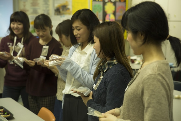 Students from Bunkyo Women's University in Hiroshima, Japan, receive American treats from Matthew C. Perry High School students at Marine Corps Air Station Iwakuni, Nov 23., 2015. Bunkyo Women's University students visited M.C. Perry High School to teach the students various Japanese traditions like brewing tea and dancing. Visits like these allow both parties to learn and respect how the other lives.