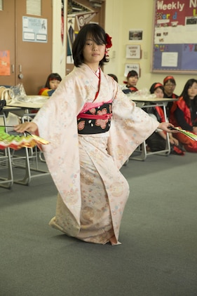 Yuki Kintanaka, a student at Bunkyo Women's University in Hiroshima, Japan, performs a traditional dance for Matthew C. Perry High School students at Marine Corps Air Station Iwakuni, Nov. 23, 2015. Bunkyo Women's University students visited the station to learn about American culture as well as teach the American students a little about their own. School trips like this help the bond between Japan and the U.S. grow stronger.