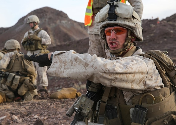 Cpl. Garrett Schroll gives the traverse hand-and-arm signal to his team during the company supported, live-fire assault portion of a Marine Corps Combat Readiness Evaluation at Marine Corps Air Ground Combat Center Twentynine Palms, Calif., Dec. 6, 2015. The purpose of a MCCRE is to evaluate Marines' collective performance in specific mission requirements that will prepare them for their upcoming deployment rotation. Schroll is a machine gunner, with 2nd Battalion, 7th Marine Regiment, 1st Marine Division. (U.S. Marine Corps photo by Lance Cpl. Devan K. Gowans)