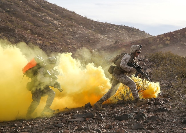 Marines run through the obstruction of smoke during the company supported, live-fire assault portion of a Marine Corps Combat Readiness Evaluation at Marine Corps Air Ground Combat Center Twentynine Palms, Calif., Dec. 6, 2015. The purpose of a MCCRE is to evaluate Marines' collective performance in specific mission requirements that will prepare them for their upcoming deployment rotation. The Marines are with 2nd Battalion, 7th Marine Regiment, 1st Marine Division. (U.S. Marine Corps photo by Lance Cpl. Devan K. Gowans)