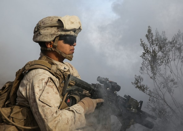 A Marine conceals himself under the obstruction of deployed smoke during the company supported, live-fire assault portion of a Marine Corps Combat Readiness Evaluation at Marine Corps Air Ground Combat Center Twentynine Palms, Calif., Dec. 6, 2015. The purpose of a MCCRE is to evaluate Marines' collective performance in specific mission requirements that will prepare them for their upcoming deployment rotation. The Marine is with 2nd Battalion, 7th Marine Regiment, 1st Marine Division. (U.S. Marine Corps photo by Lance Cpl. Devan K. Gowans)