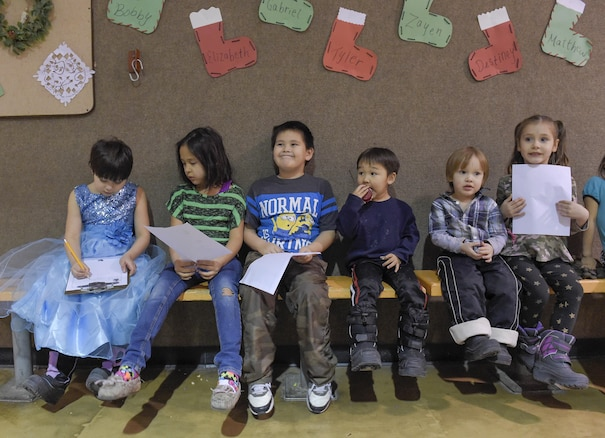 Children hold their their Christmas lists while awaiting toys from Santa Claus, played by Marine Corps Sgt. Mauricio Sandoval, during a Toys for Tots event in Nikolai, Alaska, Dec. 11, 2015. U.S. Air Force photo by Alejandro Pena